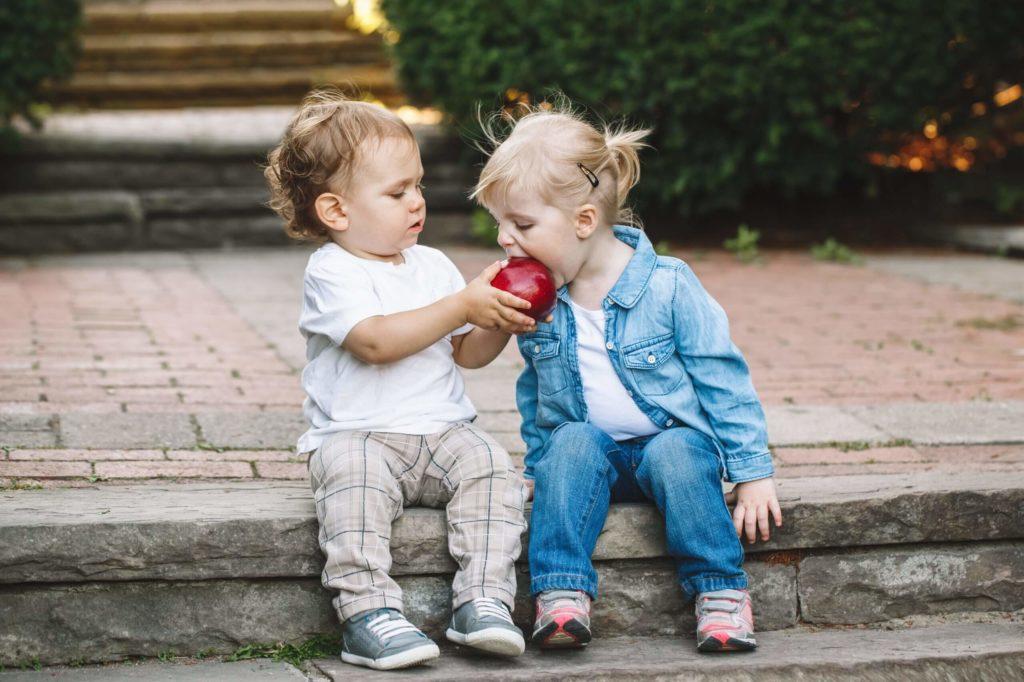 Ребенок делится яблоком